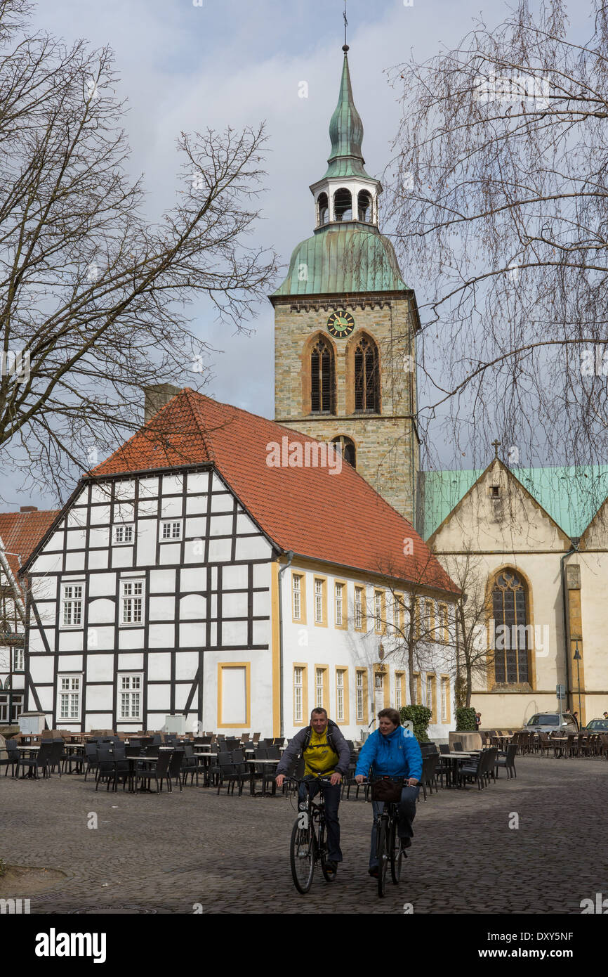 Cyclists pass through the town of Wiedenbrück, Nordrhein Westfalen, Germany - Stock Image