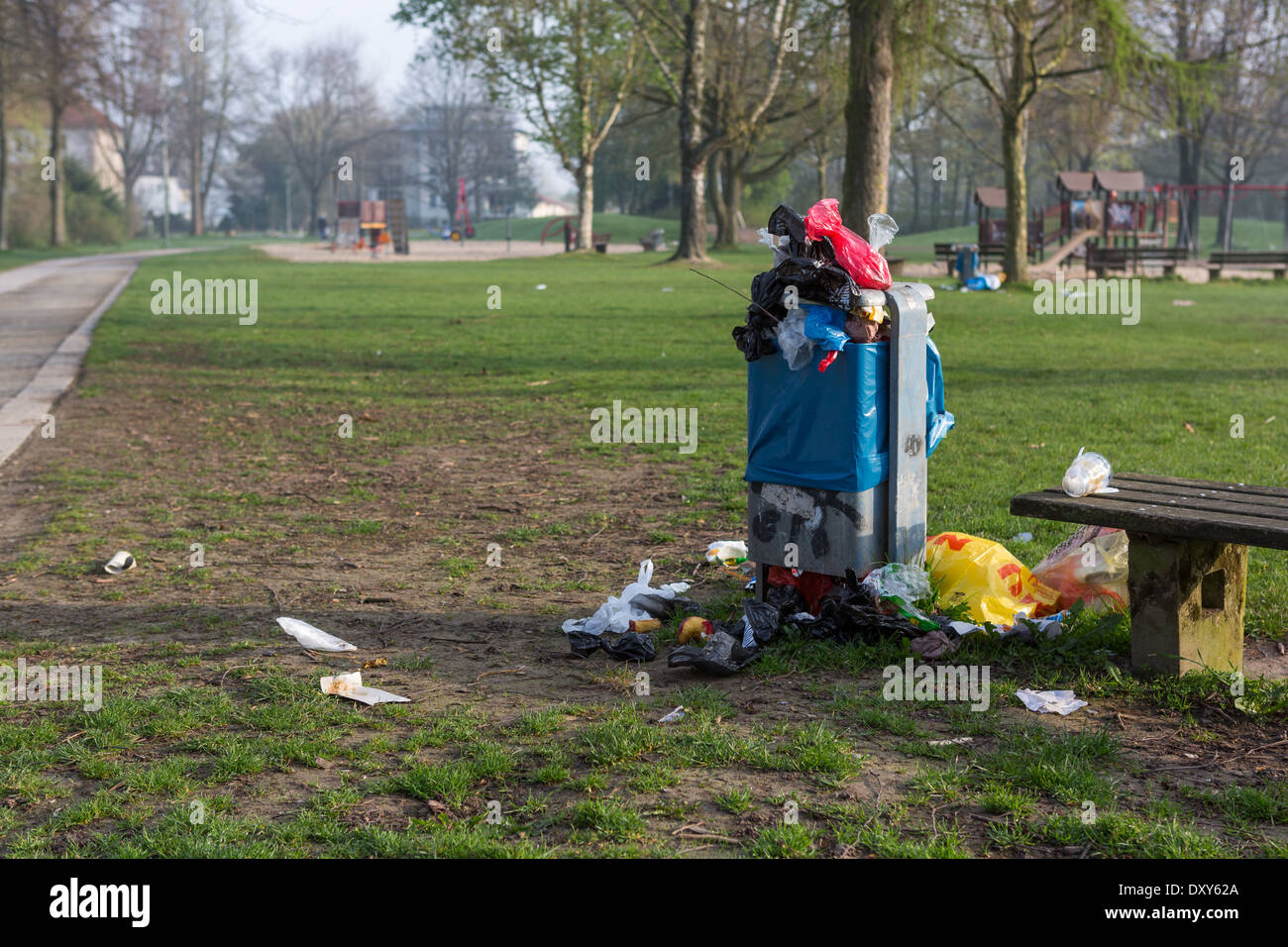 Overflowing rubbish bin in a children's playground - Stock Image