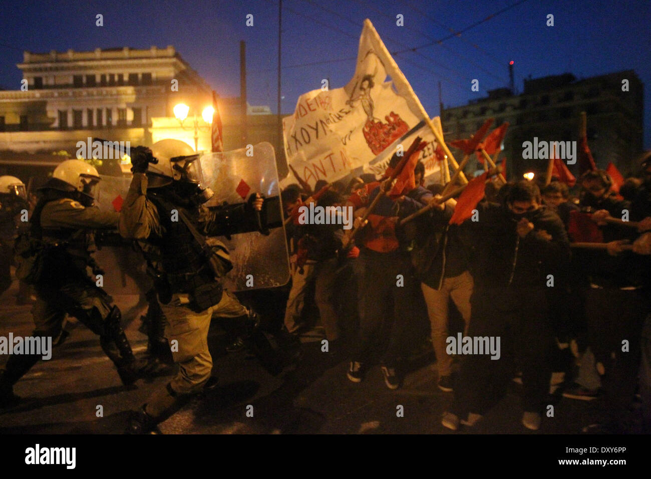 Athens, Greece. 1st Apr, 2014. Protesters clash with riot police blocking the way to the parliament in Athens, Greece, on April 1, 2014. Greek authorities set up exclusion zones in central Athens in which all protests are banned because of the ongoing Eurogroup meeting attended by all European Union finance ministers. Nevertheless, some 7,500 anti-austerity demonstrators held three separate protests outside the exclusion zones, and some tried to break through the riot police cordon blocking their way to the parliament. Credit:  Marios Lolos/Xinhua/Alamy Live News - Stock Image