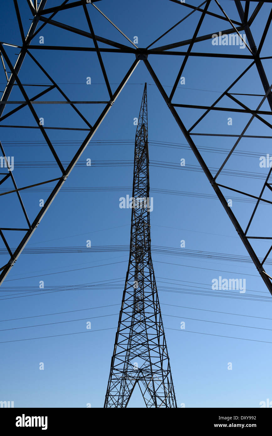 Three symmetrical steel lattice electric towers with high tension power lines Ontario Hydro - Stock Image