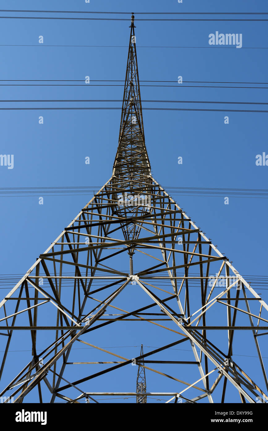 Looking up a symmetrical steel lattice electric tower with high tension power lines against a blue sky Ontario Hydro - Stock Image