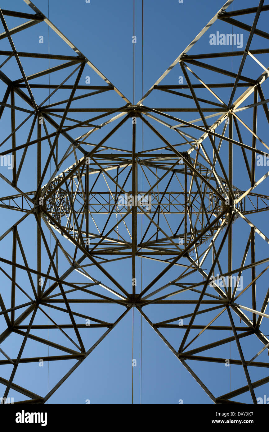 Abstract symmetrical latticework looking up a steel suspension electric tower with high tension power lines and a blue sky Ontario Hydro - Stock Image