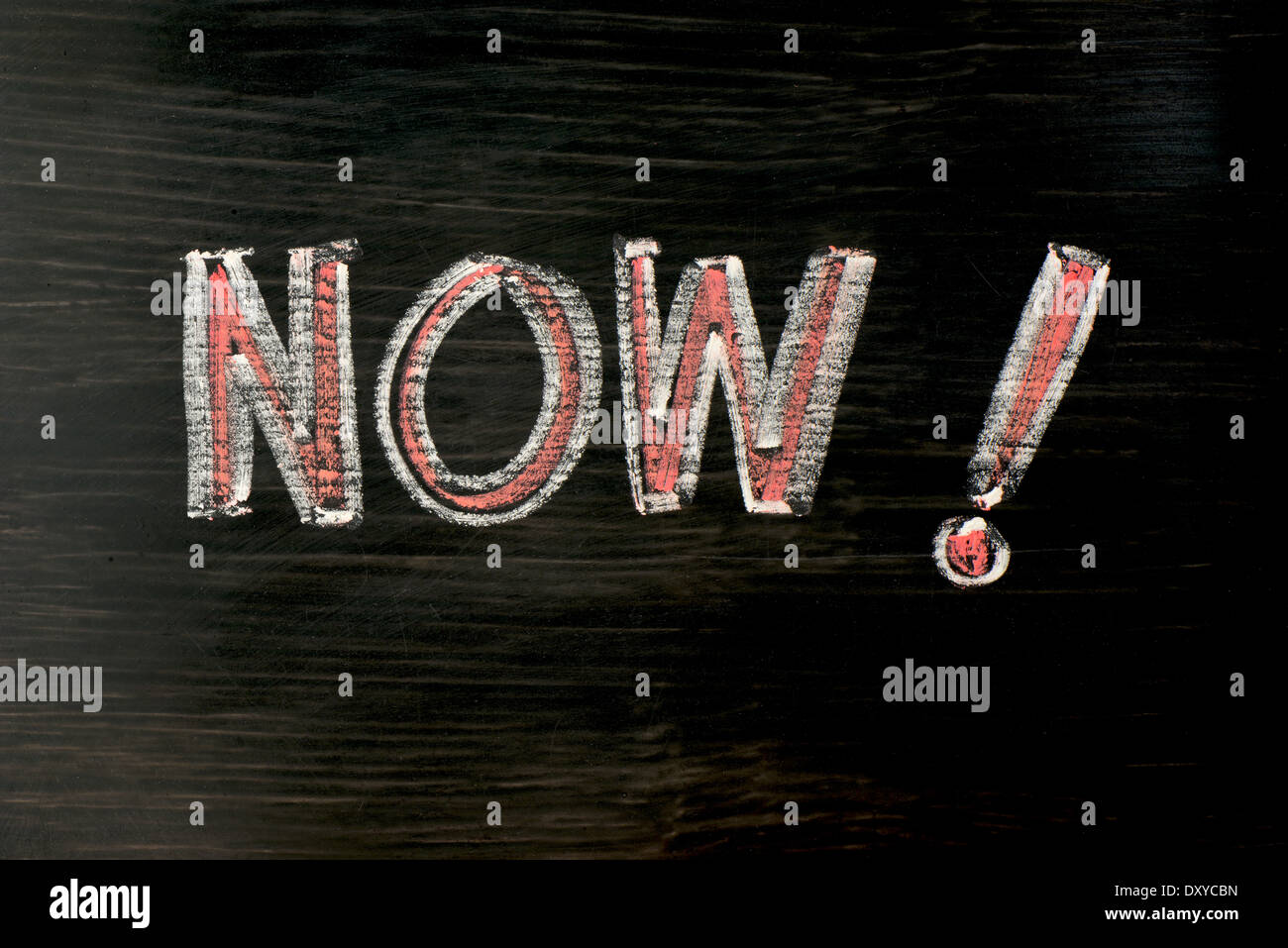 NOW- word written with chalk on a blackboard - Stock Image