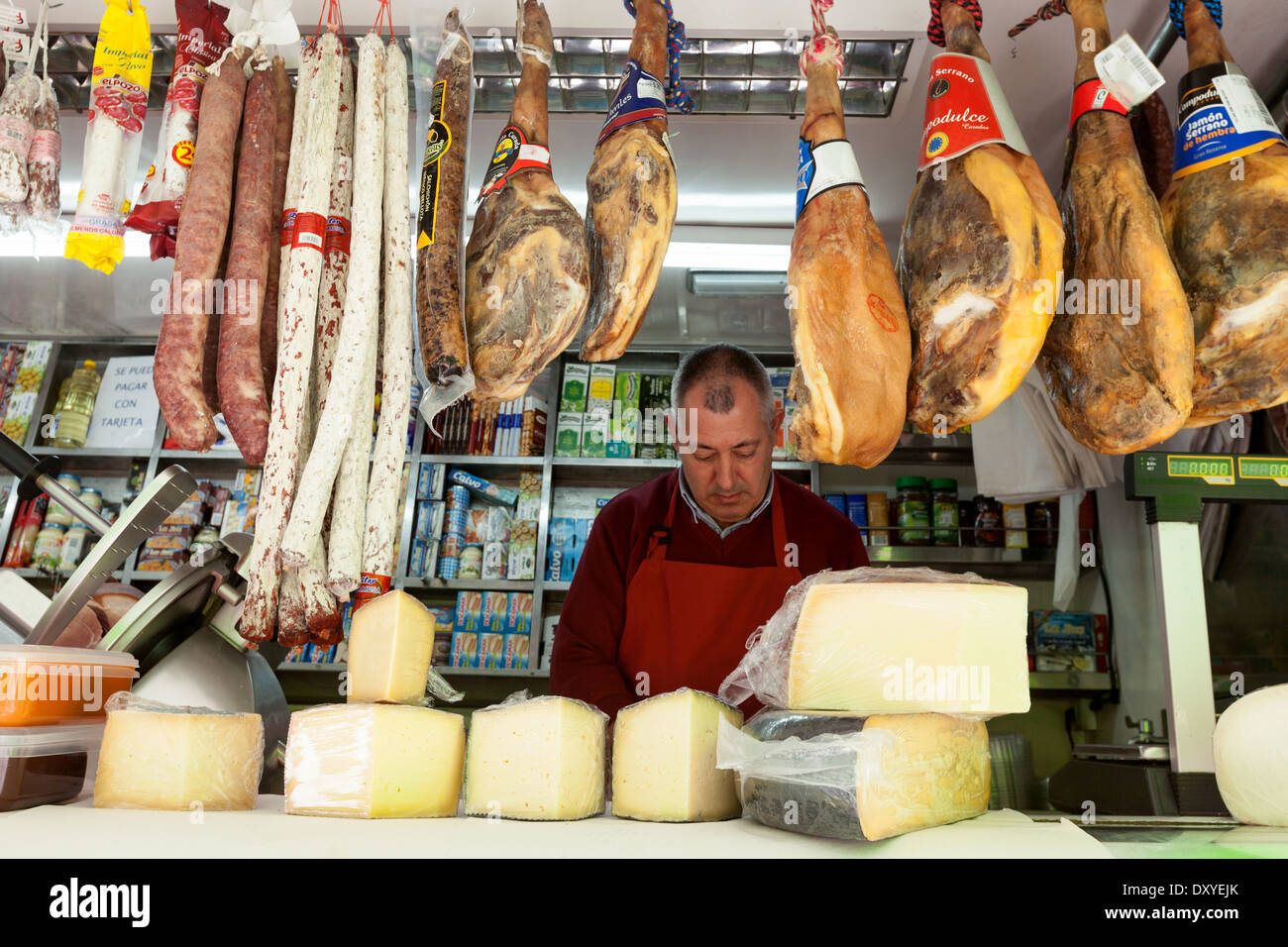 Food market Spain; A butcher selling meat and cheese in his food stall, Turre market, Almeria Andalusia Spain Europe - Stock Image