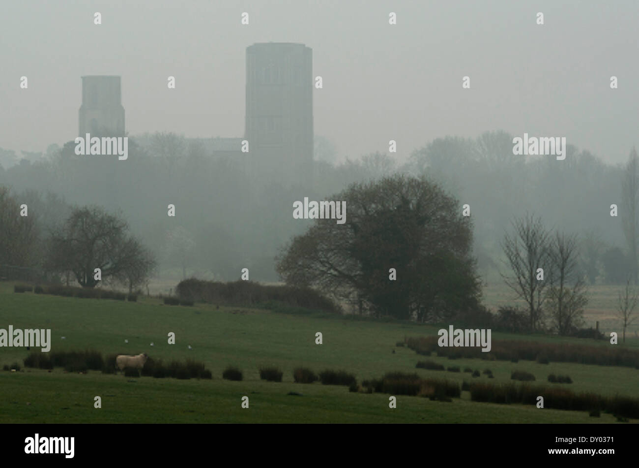WYMONDHAM, Norfolk, UK, 2nd April 2014. Wymondham Abbey, the 900-year old parish church of the Norfolk market town, looms out of the morning mist. The East Anglian region is expected to see air pollution levels peak due to a combination of light winds, dust from Saharan Africa, and industrial pollution, according to a forecast from the UK Government's  Department for Environment, Food and Rural Affairs (DEFRA). Credit:  Keith Whitmore/Alamy Live News - Stock Image