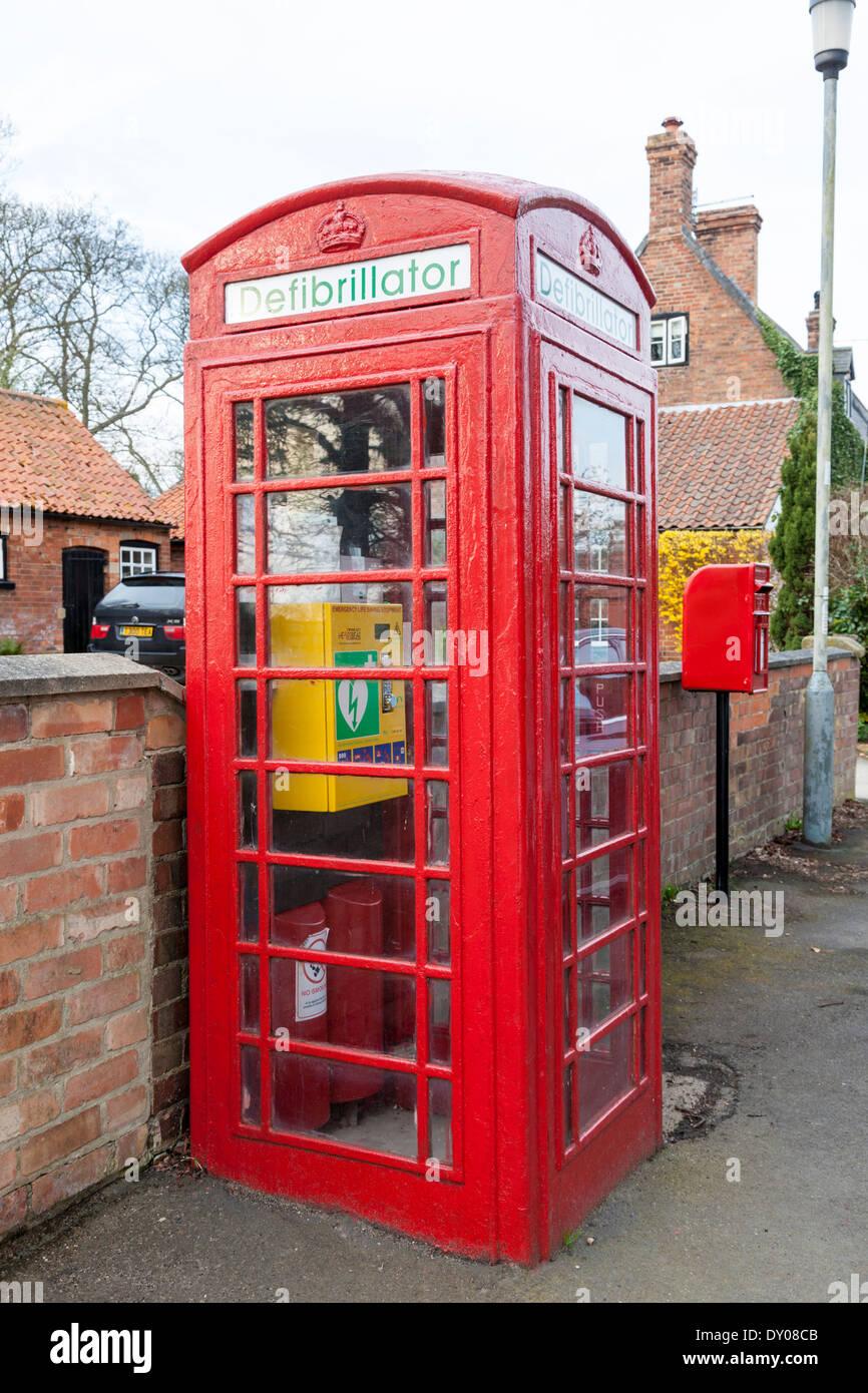 Defibrillator. Old phone box now used to keep emergency life saving equipment, Nottinghamshire, England, UK - Stock Image