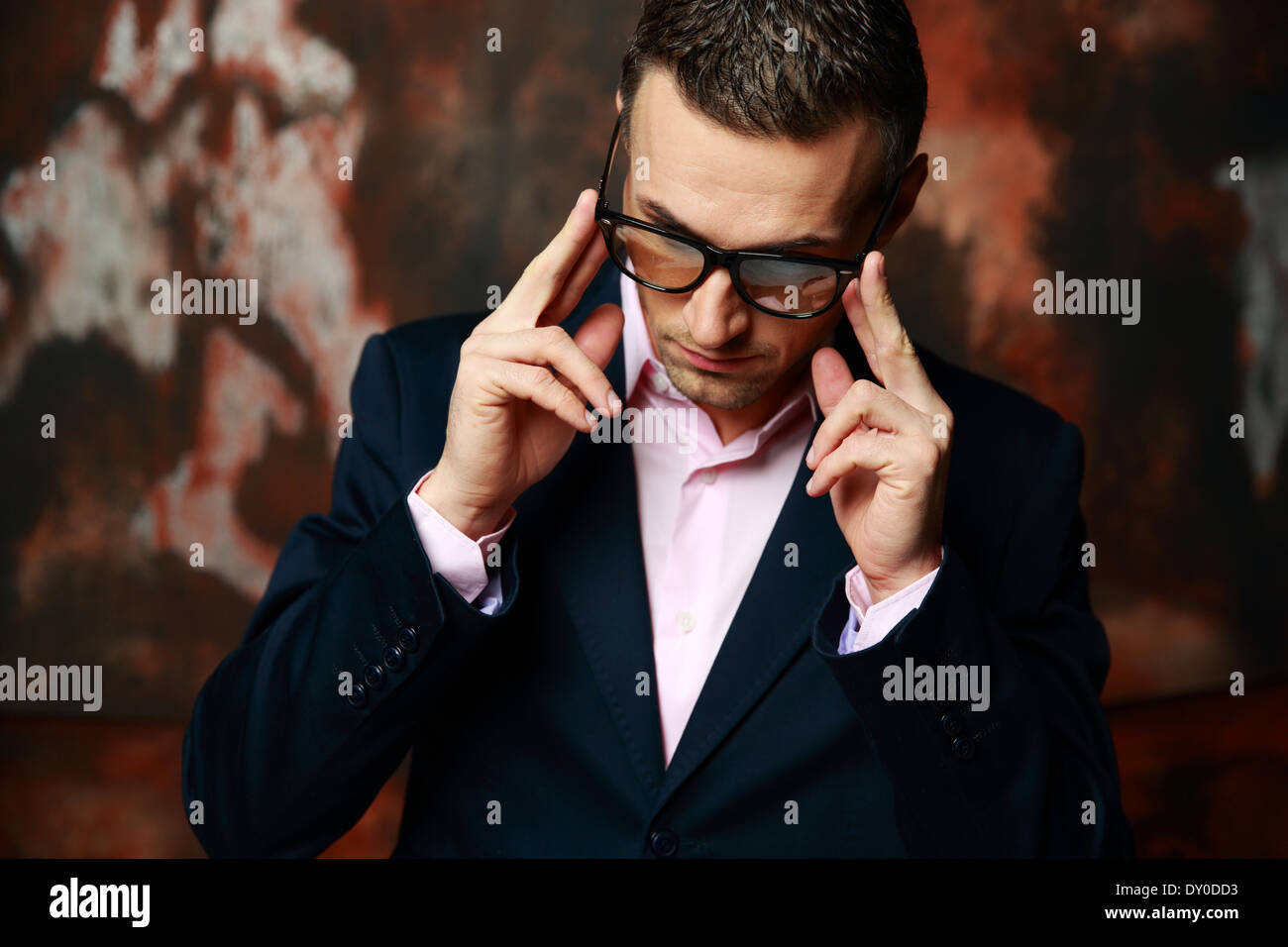 Cool fashion man in glasses standing over industrial background - Stock Image