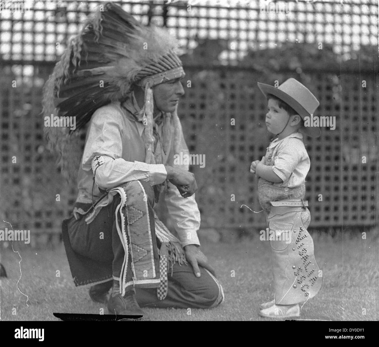 Visiting Indian Chief High Eagle talks with Johnny Schneider (aged about 3 or 4 and dressed in cowboy outfit), White City, Sydney, 11 Jan 1935 / photographer Sam Hood - Stock Image