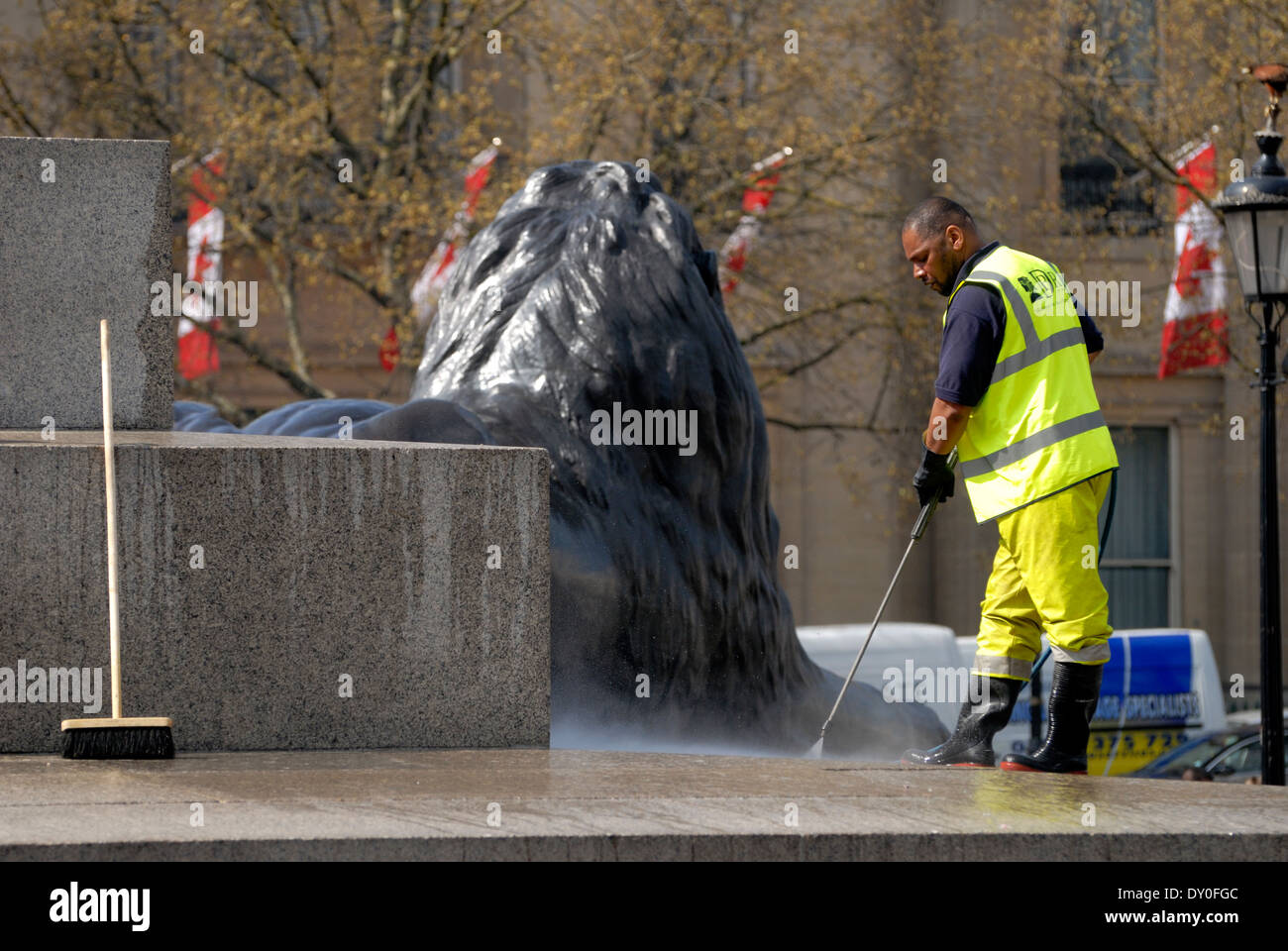 London, England, UK. Worker in hi-vis jacket cleaning the base of Nelson's Column with a power hose - Stock Image