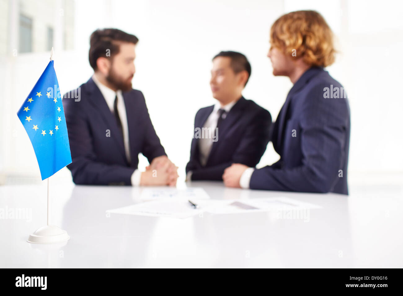 Image of European flag on workplace with three partners negotiating on background - Stock Image