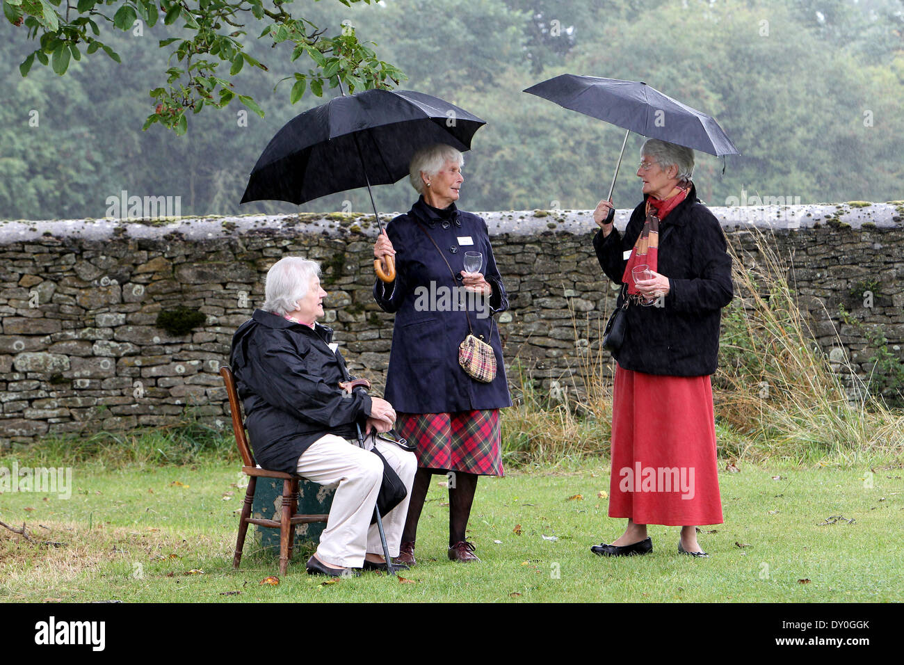 Visitors shelter from the rain at an outdoor reception for British Prime Minister David Cameron in his Witney constituency - Stock Image