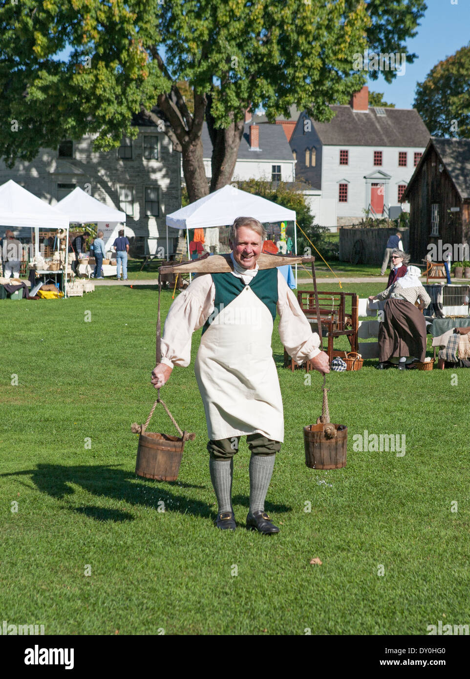 Man carrying buckets using a yoke and wearing period dress Strawbery Banke Museum Portsmouth New Hampshire, New England, USA - Stock Image