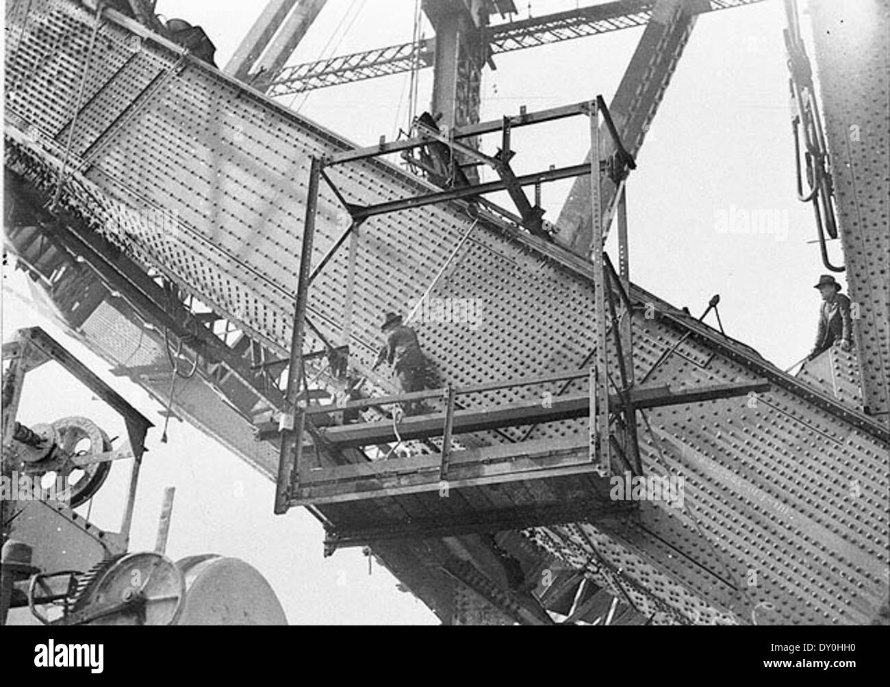 Riggers riveting the red-hot rivets on the lower outside south chord, Sydney Harbour Bridge, 1930-1931 / Sam Hood - Stock Image