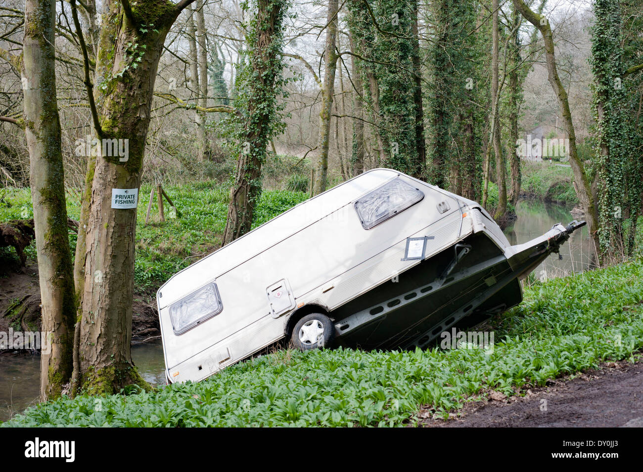 A caravan which has become stuck in the Little Avon river at Damery in Gloucestershire UK - Stock Image