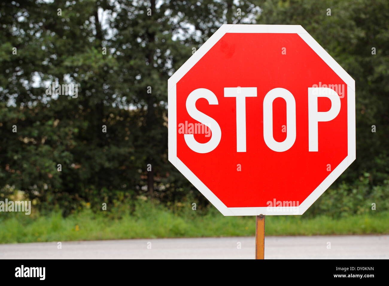 old STOP traffic sign at the side of a road. - Stock Image