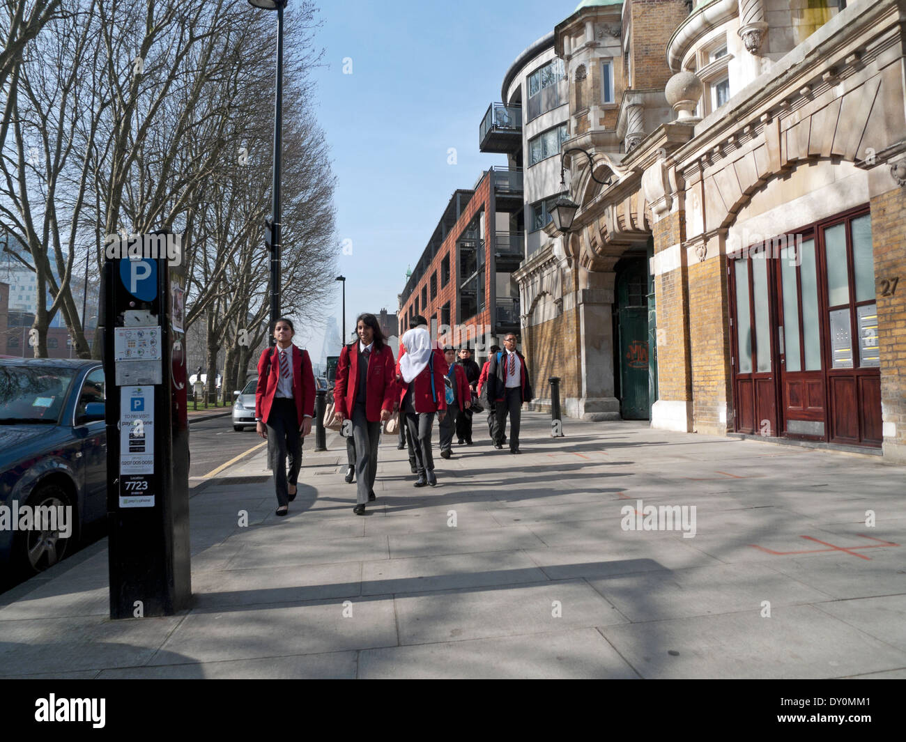 Schoolchildren in uniform walking together along Mile End Road in Whitechapel London KATHY DEWITT - Stock Image
