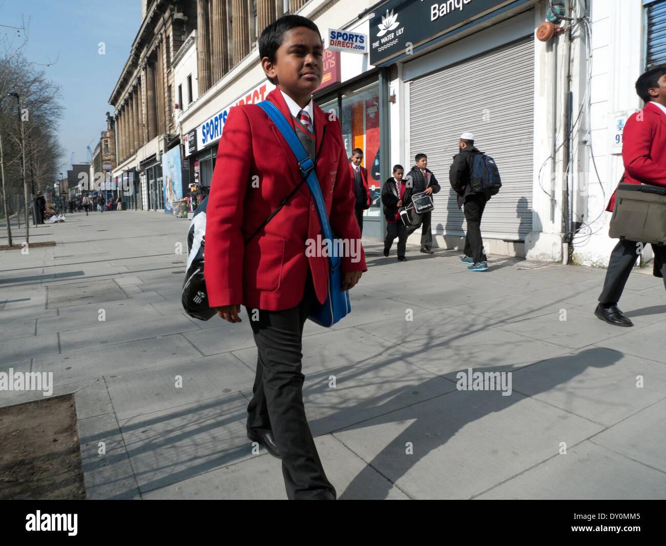 Boy in uniform walking to school along Mile End Road in Whitechapel London   KATHY DEWITT - Stock Image