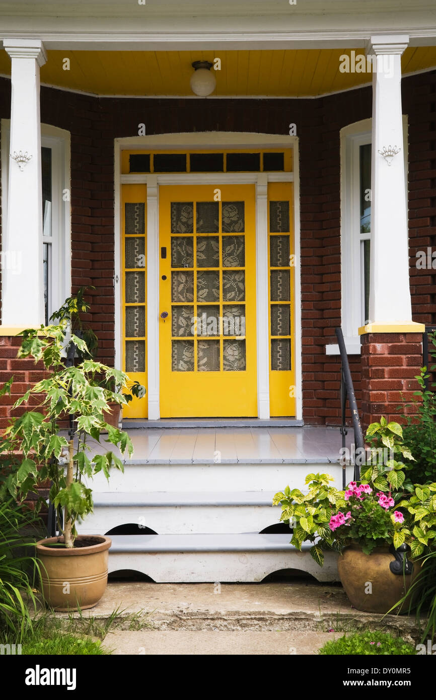Yellow Entrance Door And Porch On A Residential Red Brick Home Stock