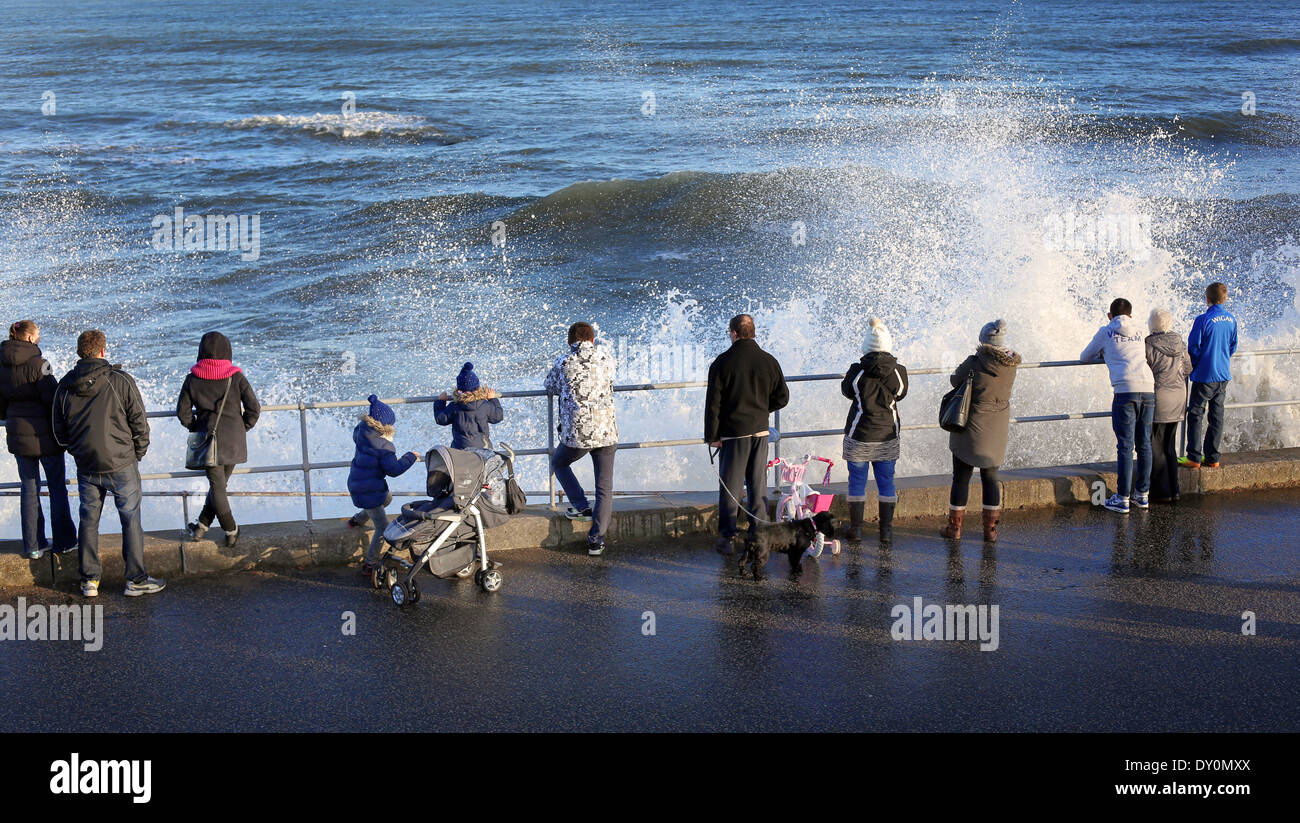People watch the waves batter the shore in Aberdeen, Scotland, UK - Stock Image