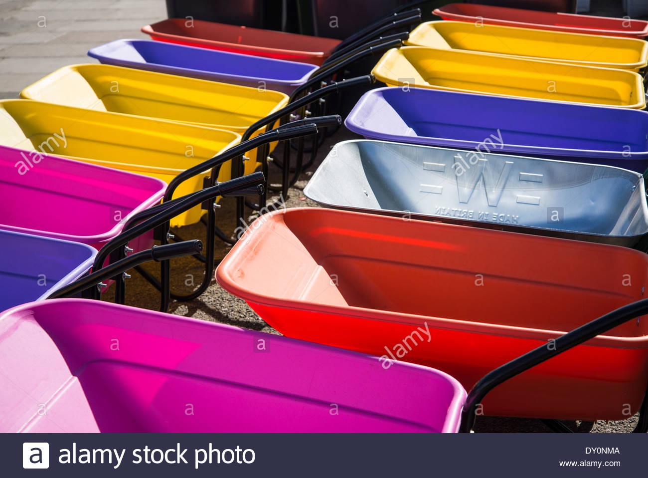 Colourful wheelbarrows - Stock Image
