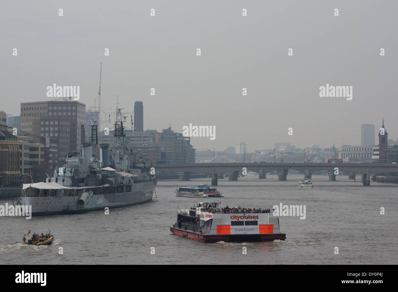 London, UK. 2nd April 2014. Beyond HMS Belfast, central London lies under a blanket of atmospheric haze as the Met Office forecasts severe smog in London this week due to a combination of air pollution, light south easterly winds and a Saharan storm which is depositing fine red dust into the atmosphere. Defra's Daily Air Quality Index advised those with poor health or lung conditions to avoid strenuous outdoor exercise, and asthma sufferers should make sure they have their inhaler to hand. Credit:  Patricia Phillips/Alamy Live News - Stock Image