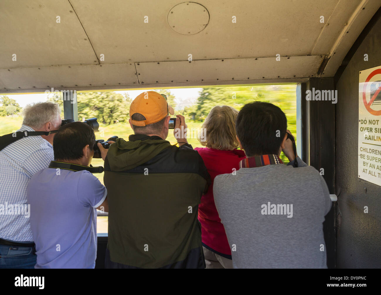 Tourists taking photographs from a train window - Stock Image