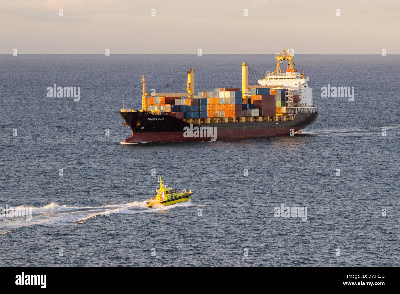 Cargo container ship with yellow pilot boat approaching at dusk - Stock Image