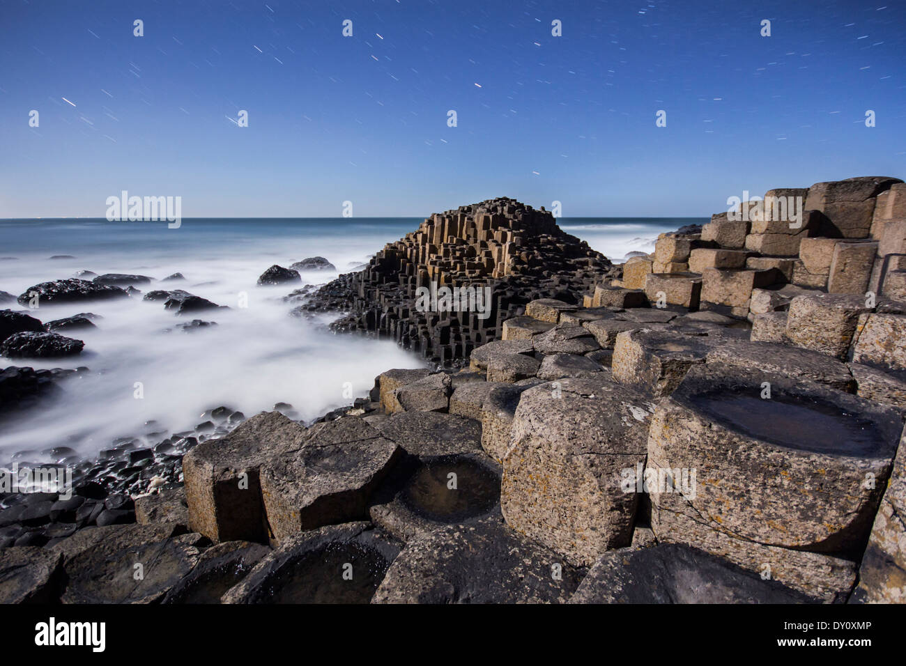 Starry night above the moonlit basalt columns at the Giant's Causeway UNESCO World Heritage site. - Stock Image