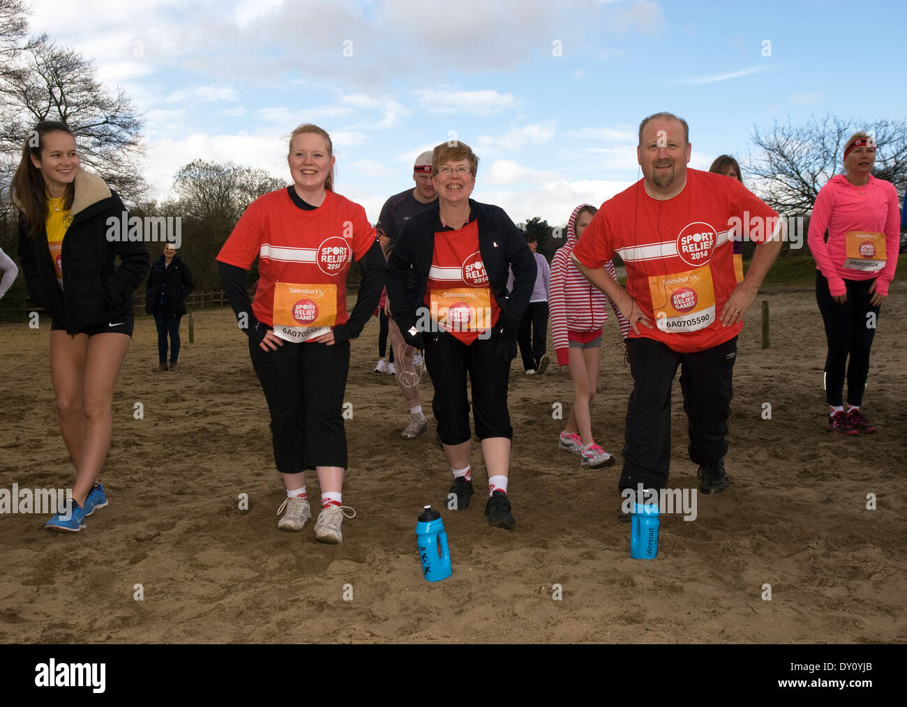 Volunteer runners for Sport Relief 2014 warming up prior to the race, Frensham, UK. - Stock Image