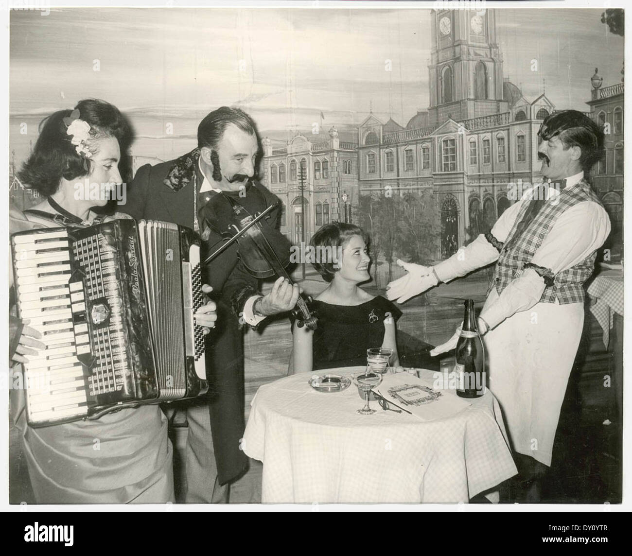 Elizabeth Connelly, TWA air hostess froom New York serenaded by head waiter with Mr & Mrs George Miller playing the violin and accordion respectively, Music Hall Restaurant, Apr 1965 - Stock Image
