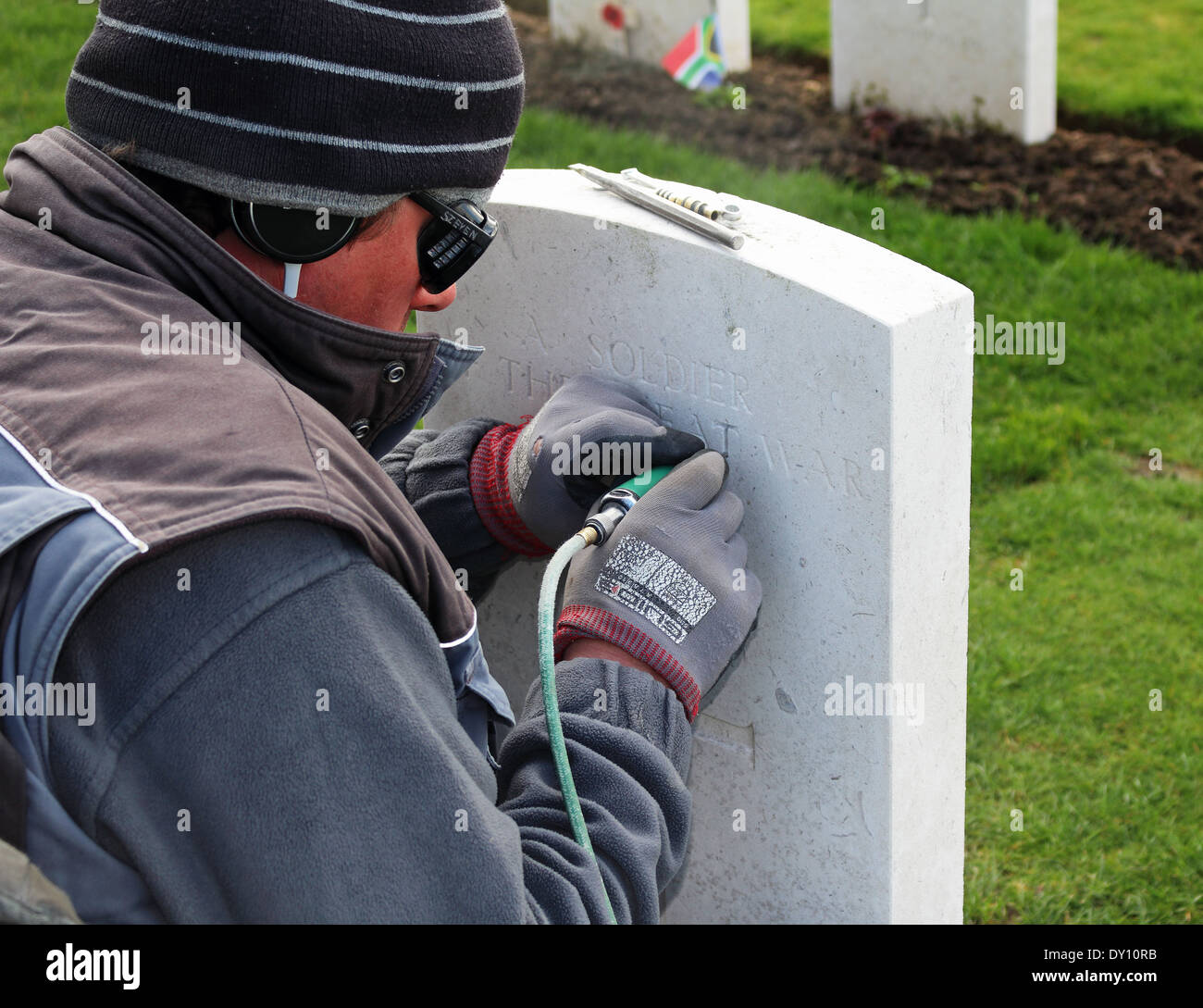 Workman engraving a World War 1 Soldiers Headstone in a War Cemetery in Flanders, Belgium - Stock Image