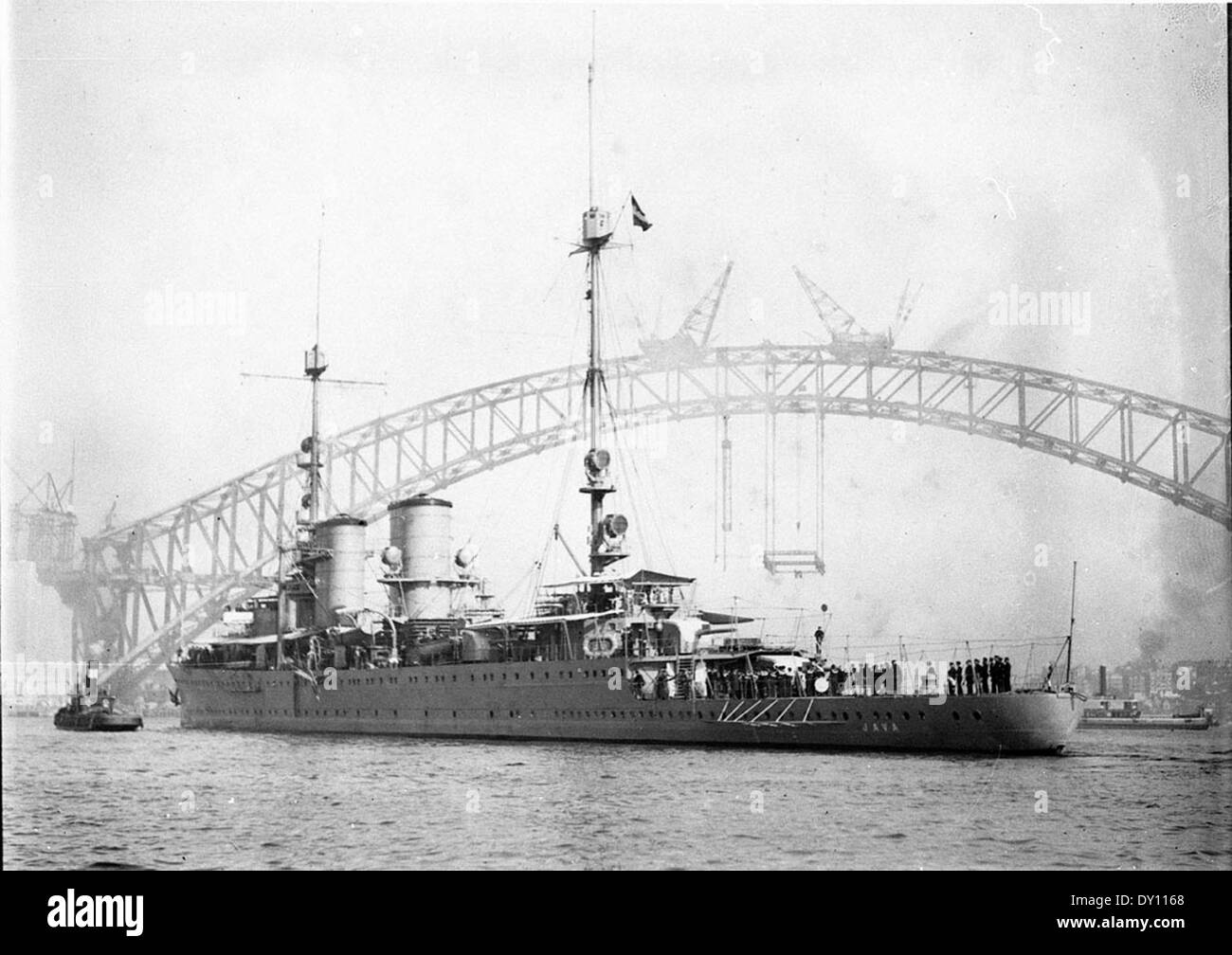 The 'Java', a warship of the Dutch East Indies, berthing with the Sydney Harbour Bridge as a background, ca. 1930 / Ted Hood - Stock Image