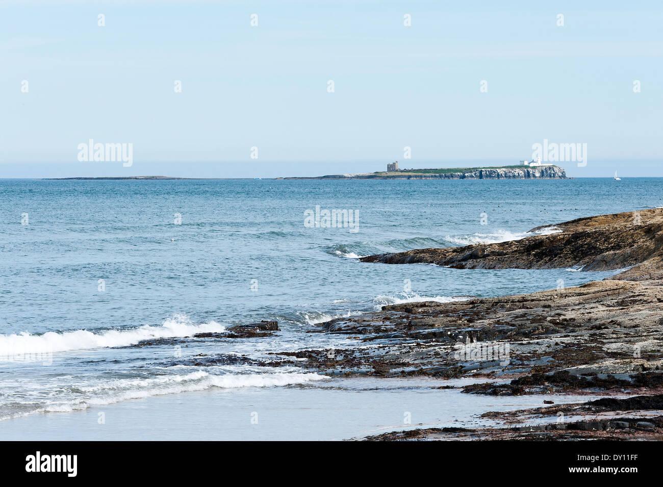 The Rocky Shoreline Near Bamburgh Northumberland with Inner Farne Island with White Lighthouse England United Kingdom Stock Photo