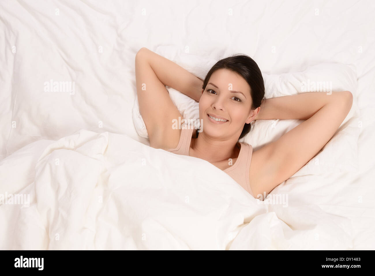 Smiling healthy rejuvenated young woman snuggling down between her pillows in bed giving the camera a wide beaming joyful smile - Stock Image