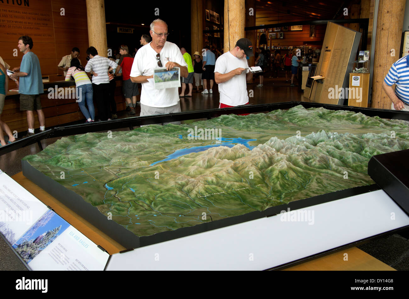 New visitors center, tourist study maps as they look at the large topographical map of the area - Stock Image