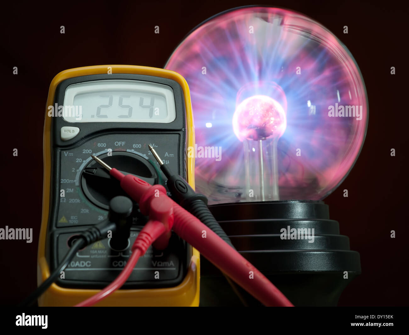 Digital multimeter and high voltage plasma lamp in the background. - Stock Image