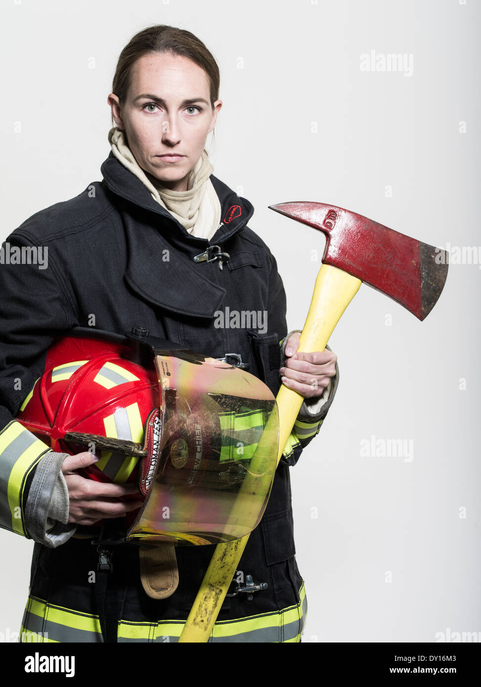 Female firefighter in structural firefighting uniform with breathing apparatus and axe Stock Photo