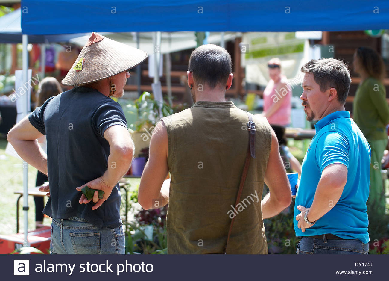 Three Caucasian men wearing casual clothes, standing together having a discussion at a primary school community day, in support of the environment. - Stock Image
