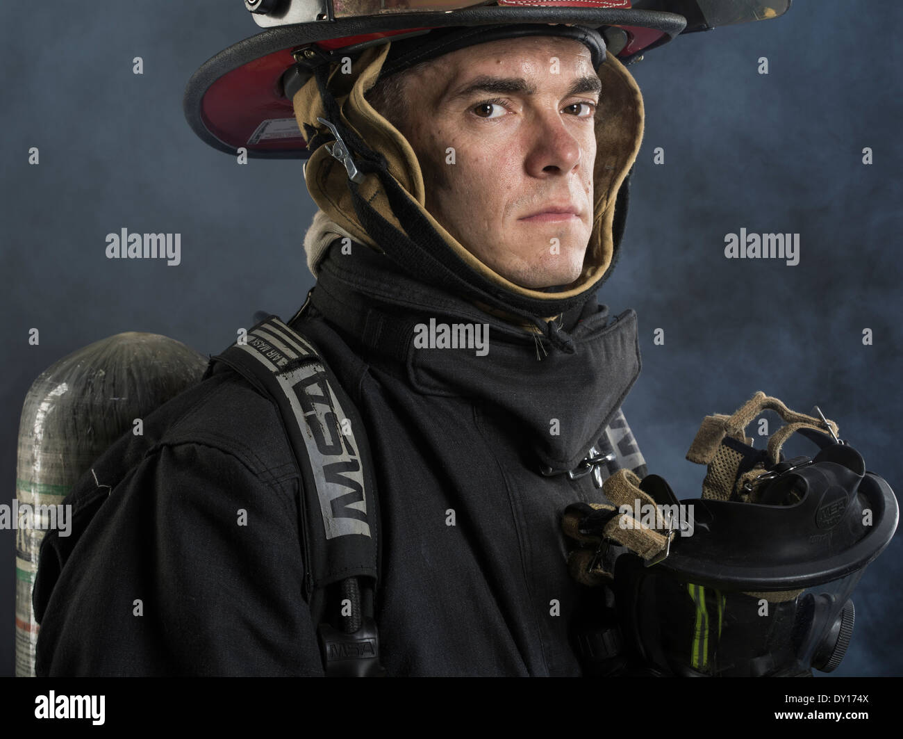 Male firefighter in structural firefighting uniform with breathing apparatus and axe - Stock Image