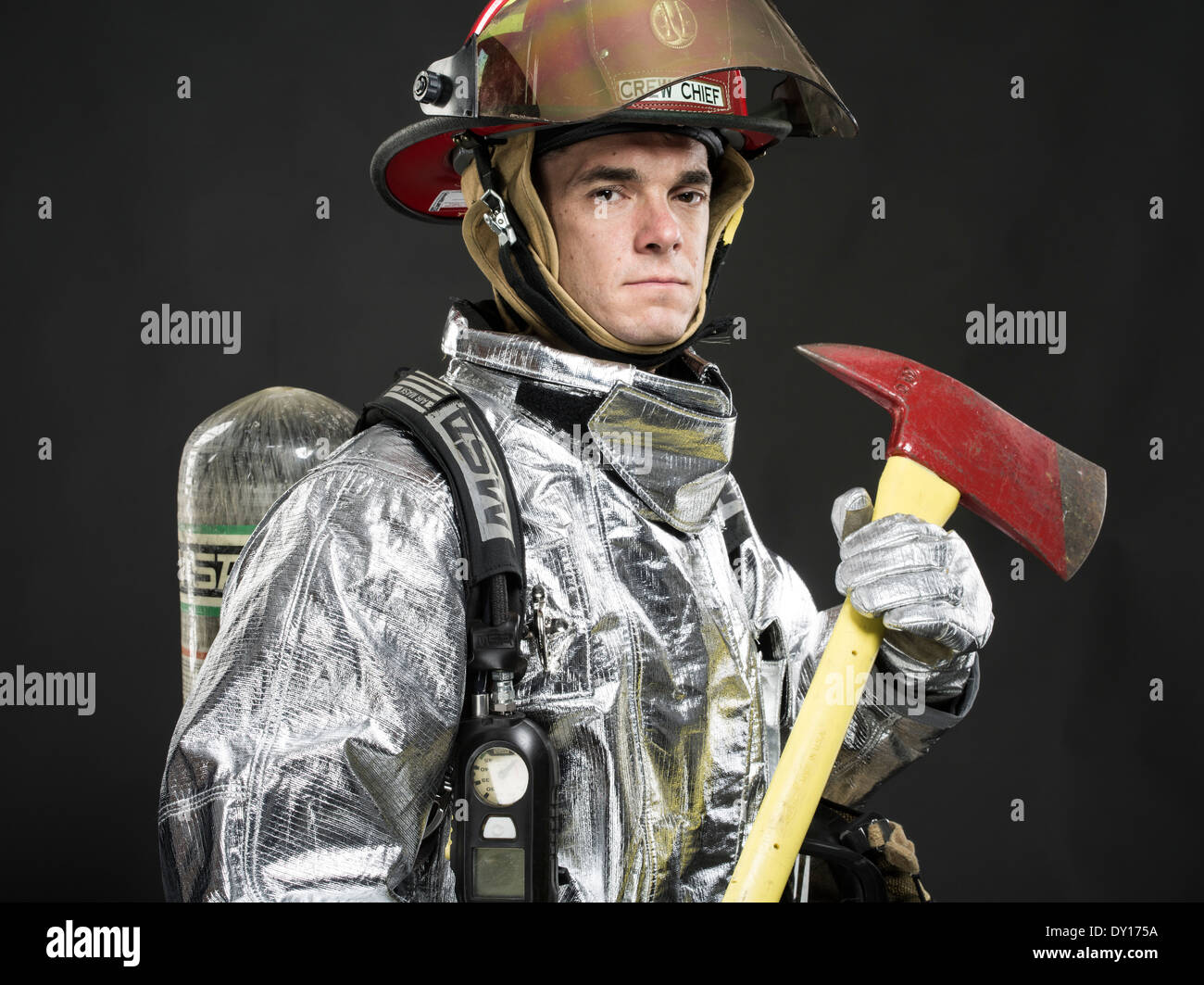 Male firefighter in high temperature aviation fuel  firefighting uniform with breathing apparatus and axe Stock Photo