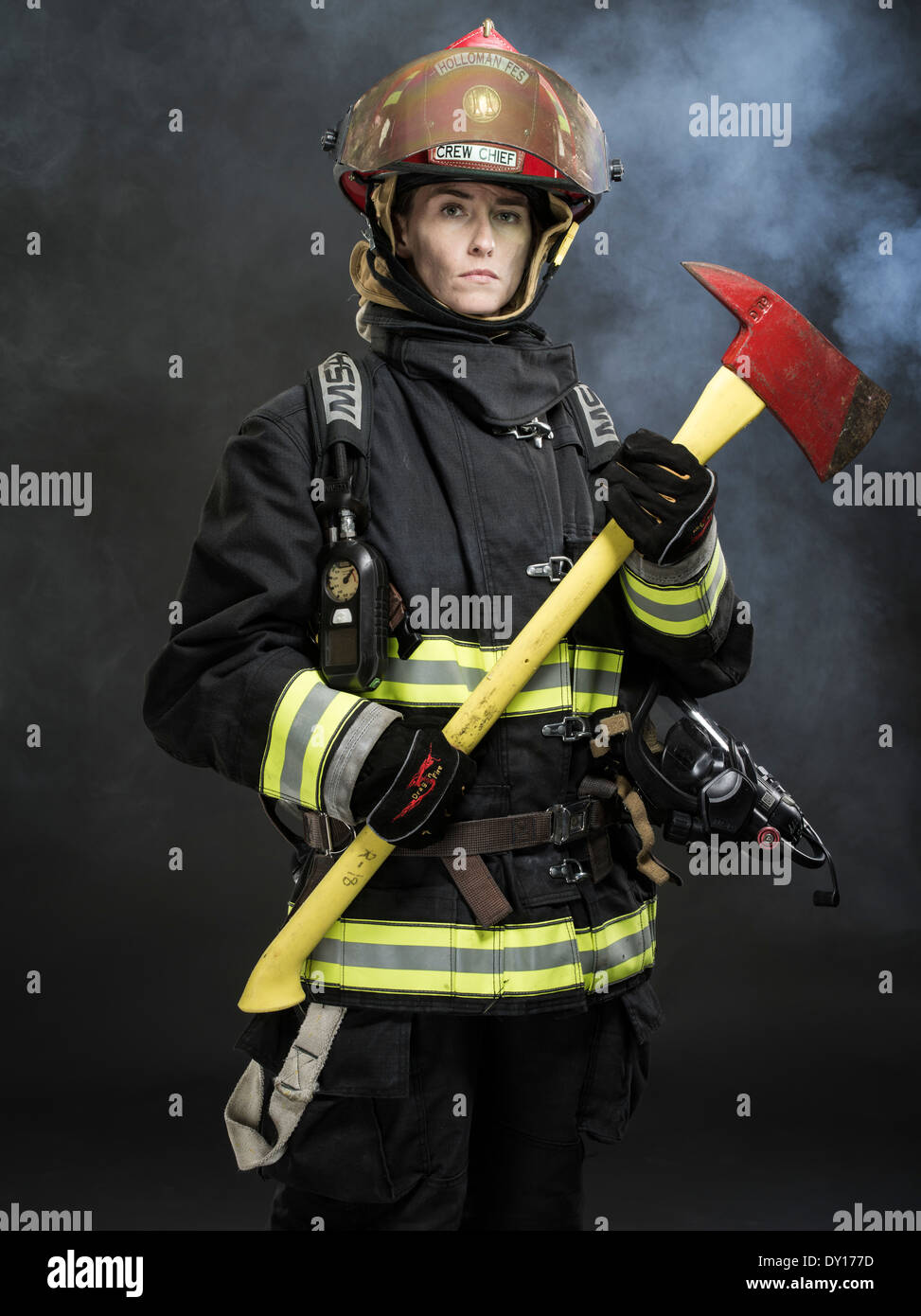 Female firefighter in structural firefighting uniform with breathing apparatus and axe - Stock Image