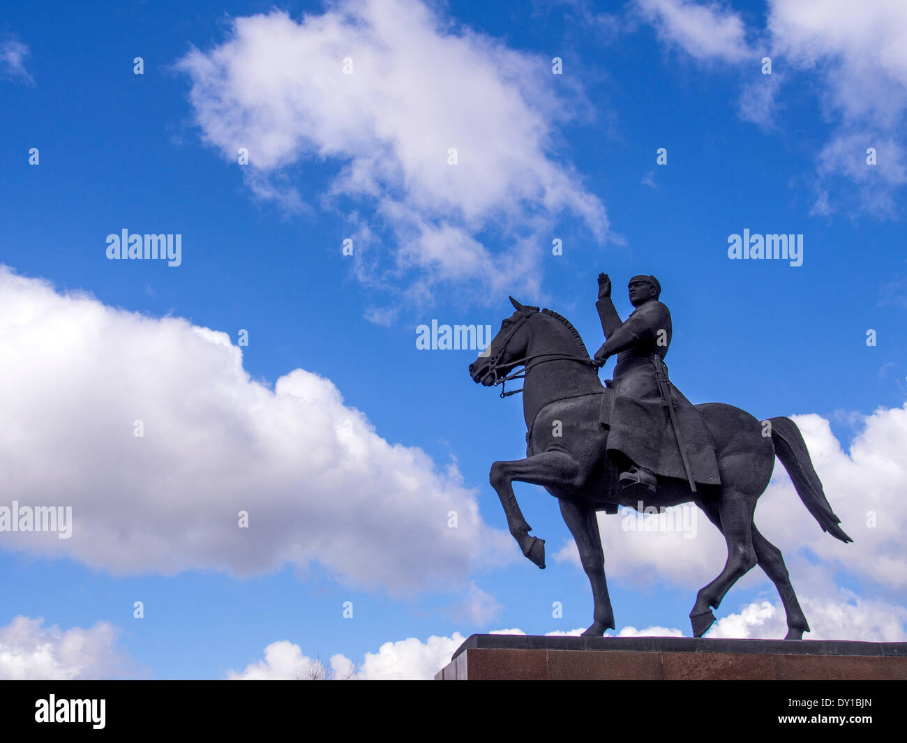 Monument Kliment Voroshilov on a horse on a background of blue sky with white clouds. Marshal Voroshilov was born Stock Photo