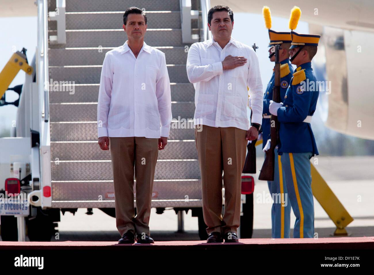 Palmerola, Honduras. 2nd Apr, 2014. Hondura's President Juan Orlando Hernandez (R) welcomes his Mexican counterpart Enrique Pena Nieto (L) at the Jose Enrique Soto Cano air base, in Palmerola, north of Tegucigalpa, Honduras, on April 2, 2014. Enrique Pena Nieto arrived in Honduras on Wednesday, to sign a joint declaration of colaboration on migration, comerce, security and tourism, among other themes with his Honduran counterpart Juan Orlando Hernandez. © Mexico's Presidency/Xinhua/Alamy Live News - Stock Image