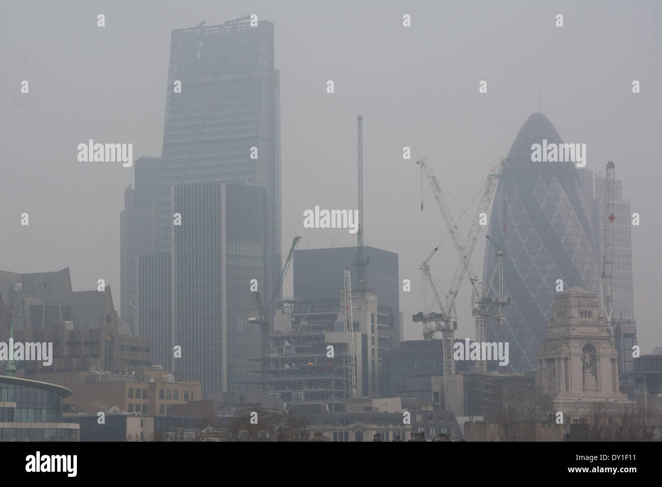 Iconic London buildings such as the Gherkin and the Cheesegrater fade behind a blanket of atmospheric pollution. - Stock Image