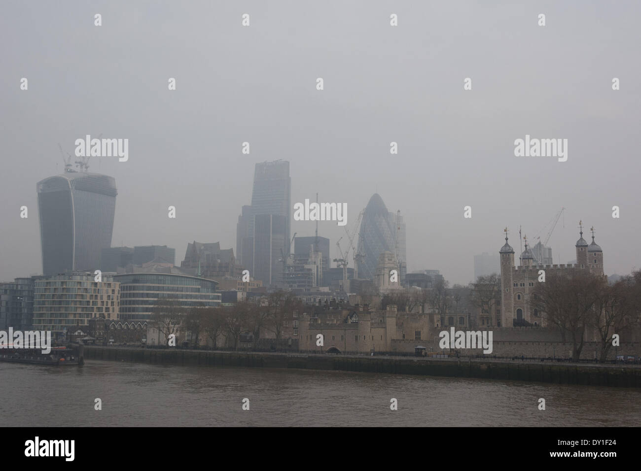 London's skyline including skyscrapers such as the Gherkin, the Walkie-Talkie, and the Tower of London lie under a blanket of smog. - Stock Image