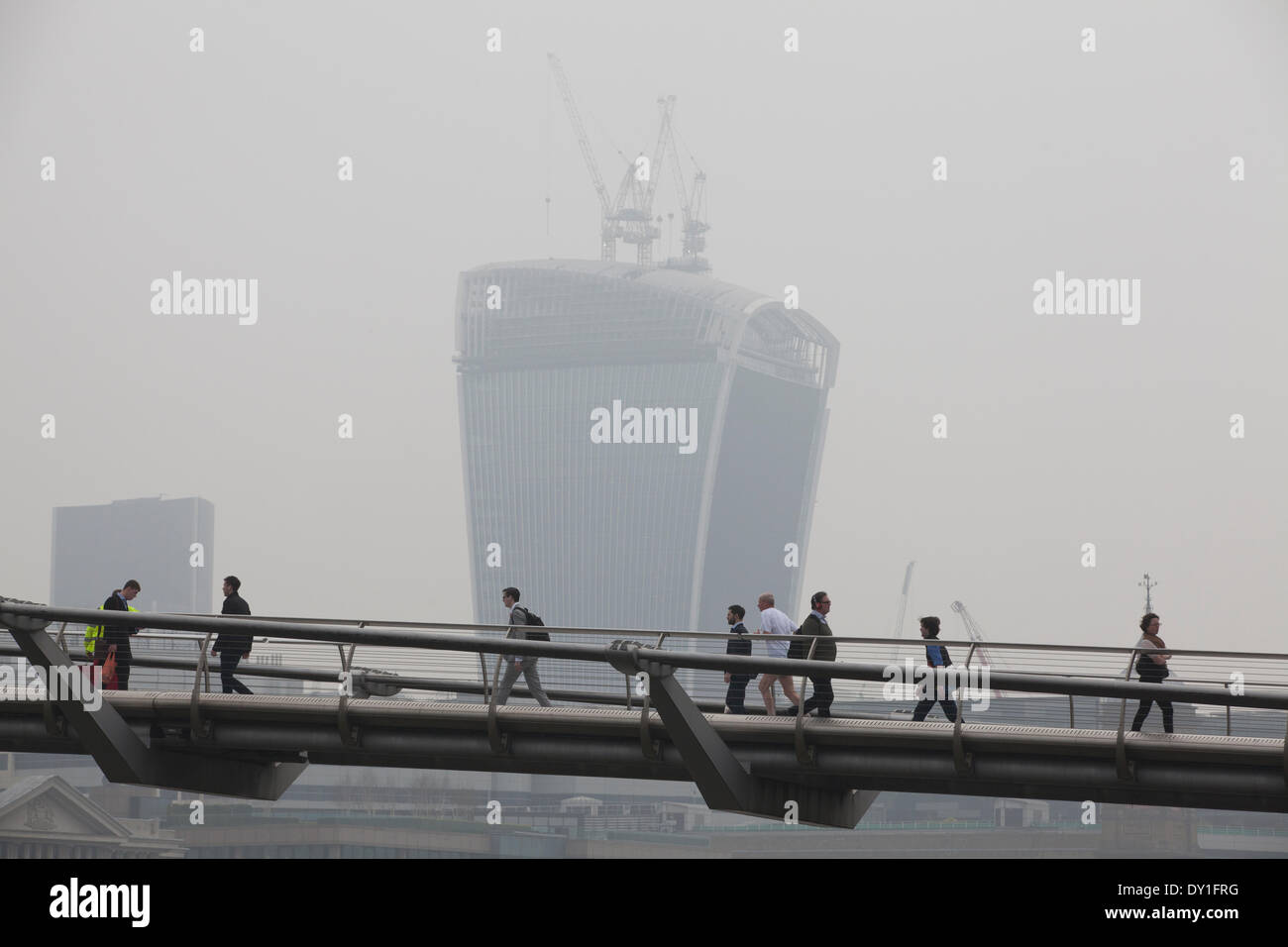 London, UK. 3rd April, 2014. London Smog: Millennium Bridge, City of London, London, UK Commuters make their way across the Millennium Bridge with the Walkie Talkie building in finance district in the background is shrouded in smog, whilst the London Smog, and red dust swept up from the Sahara continue to cause high levels of air pollution across the capital. Scores of flights have been cancelled and people have been advised to stay indoors if they suffer from asthma or heart conditions. Credit:  Jeff Gilbert/Alamy Live News - Stock Image