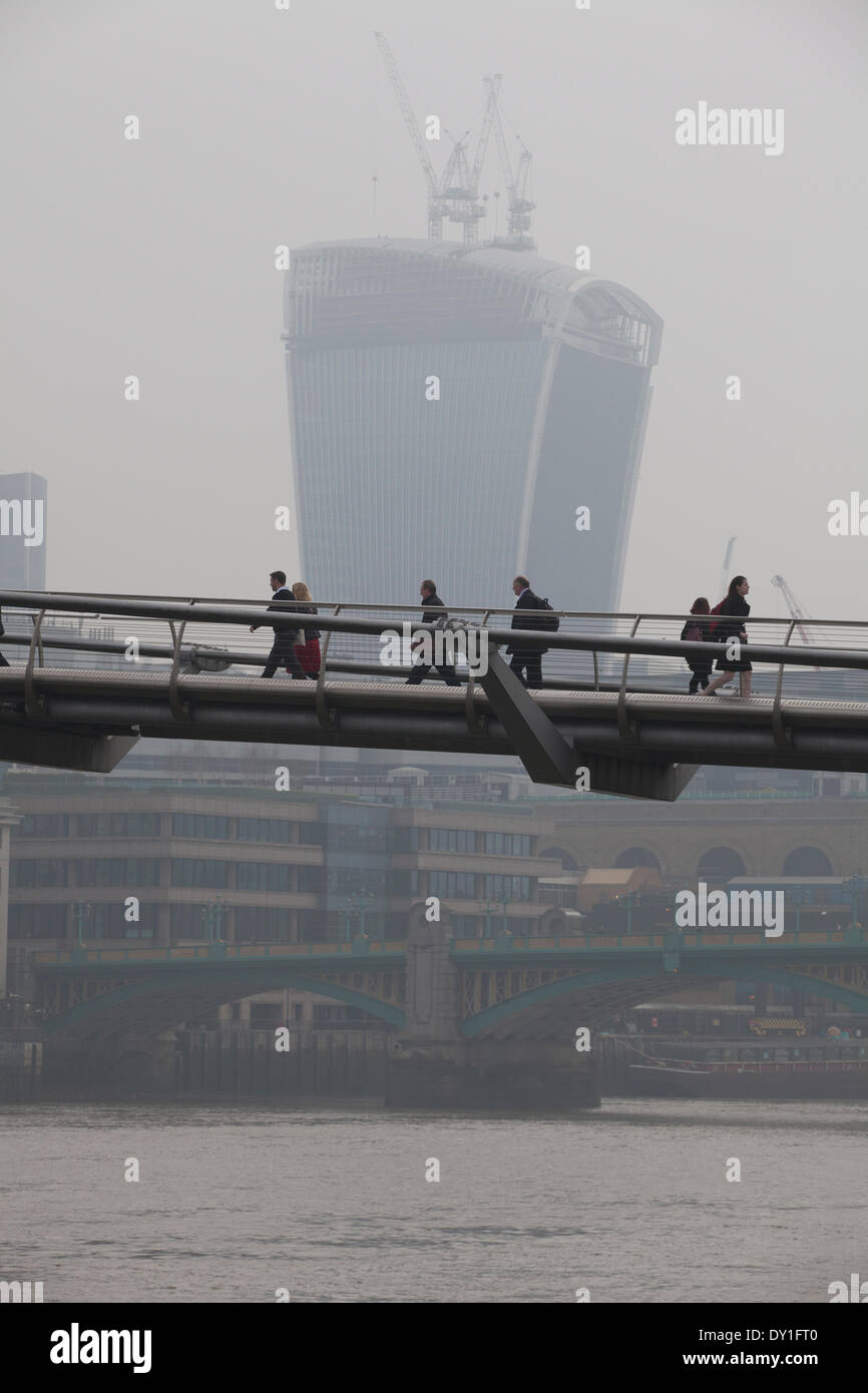 London, UK. 3rd April, 2014. London Smog: Millennium Bridge, City of London, London, UK Commuters make their way across the Millennium Bridge as the London Smog, and red dust swept up from the Sahara continue to cause high levels of air pollution across the capital. Scores of flights have been cancelled and people have been advised to stay indoors if they suffer from asthma or heart conditions. Credit:  Jeff Gilbert/Alamy Live News - Stock Image