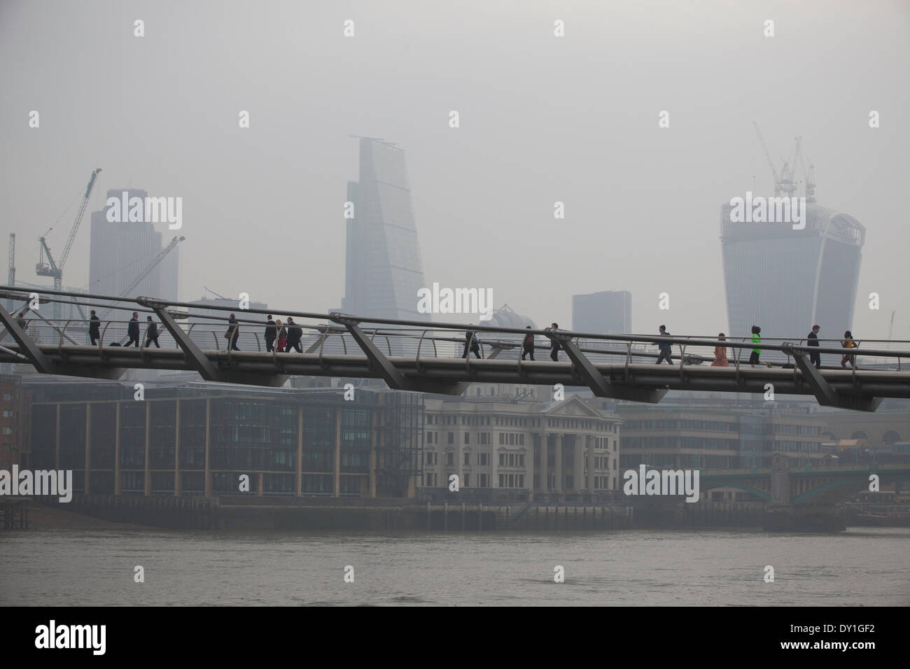 London, UK. 3rd April, 2014. London Smog: Millennium Bridge, City of London, London, UK Commuters make their way across the Millennium Bridge with the finance district in the background shrouded in smog, whilst the London Smog, and red dust swept up from the Sahara continue to cause high levels of air pollution across the capital. Scores of flights have been cancelled and people have been advised to stay indoors if they suffer from asthma or heart conditions. Credit:  Jeff Gilbert/Alamy Live News - Stock Image