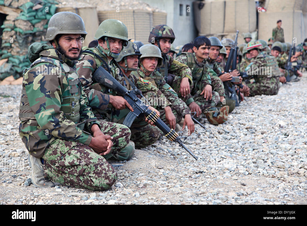 Afghan National Army soldiers wait outside during a meeting at Forward Operating Base Boris March 31, 2014 in Bermal District, Paktika province, Afghanistan. - Stock Image