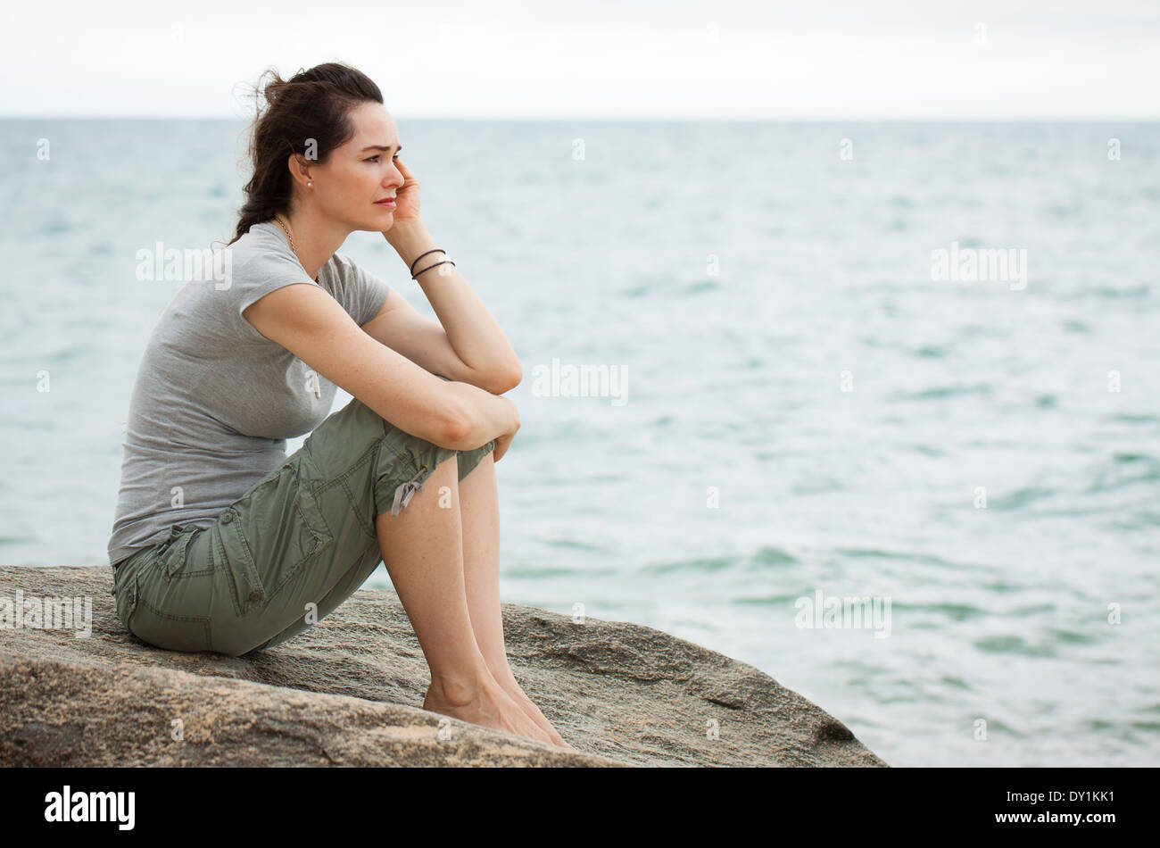 A sad and depressed woman sitting by the ocean deep in thought. - Stock Image